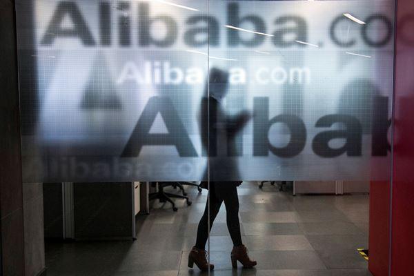 Seorang karyawan terlihat di balik dinding kaca dengan logo Alibaba di kantor pusat perusahaan itu di pinggiran Hangzhou, Provinsi Zhejiang, China. - Reuters