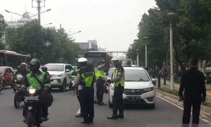 Petugas kepolisian memberhentikan kendaraan untuk mengecek kelengkapan surat- surat dalam razia gabungan yang dilakukan oleh Polres Metro Jakarta Pusat dan Samsat Jakarta Pusat di Jalan Kramat Raya, Senen, Kamis (13/2/2020).  - Antara