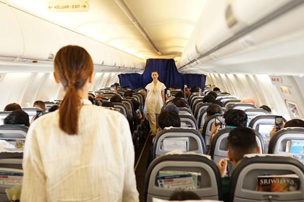 Ilustrasi - Dua pramugari melintas di lorong pesawat dalam acara Kartini Flight yang diadakan Sriwijaya Air Group, Minggu (21/42019). - Bisnis/Sriwijaya Air Group