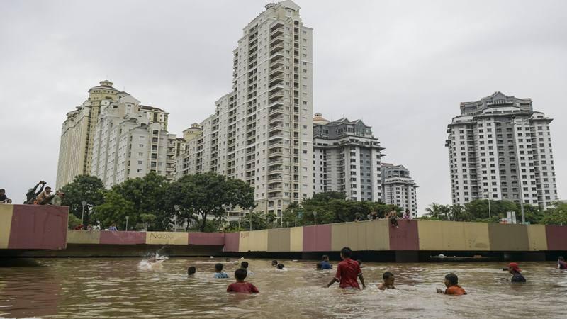 Sejumlah anak bermain saat banjir menutup terowongan di jalan Kota Baru Bandar Kemayoran, Jakarta, Jumat (24/1/2020). Banjir di kawasan tersebut diakibatkan intensitas hujan yang tinggi dan drainase yang buruk. - Antara