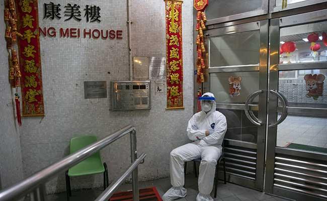 Petugas menggunakan baju khusus berjaga di luar pintu masuk ke gedung perumahan Hong Mei House di Cheung Hong Estate di distrik Tsing Yi, Hong Kong, China, Selasa (11/2/2020). Pemerintah Hong Kong mengevakuasi warga di sebuah gedung setelah dua pasien di Pusat Perlindungan Kesehatan yang berasal dari tempat tersebut terinfeksi virus corona. Bloomberg - Justin Chin