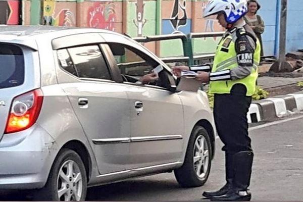 Polisi menilang pengendara yang melanggar Kawasan pembatasan Kendaraan ganjil genap di Jl Kartini Jaksel. - Twitter @tmcpoldametro