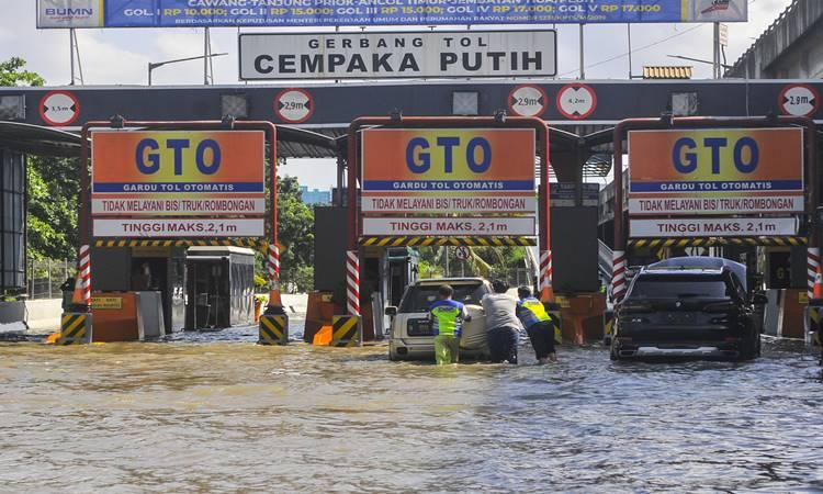Sejumlah petugas membantu mendorong mobil yang mogok akibat banjir di gerbang tol Cempaka Putih, Jakarta Pusat, Minggu (23/2/2020). Menurut petugas banjir merendam pintu tol dari jam 03.00 WIB akibat luapan air dari Waduk Ria Rio. - Antara
