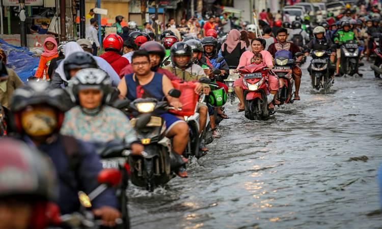 Sejumlah pengendara melintasi banjir di Jalan K.H Hasyim Ashari, Ciledug, Kota Tangerang, Banten, Selasa (25/2/2020). Hujan lebat yang mengguyur sejak Selasa (25/2) dini hari serta buruknya sistem drainase menjadi penyebab banjir di jalan tersebut. ANTARA FOTO - Fauzan