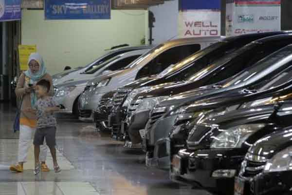 Pengunjung melintas di samping deretan bursa mobil bekas di Jakarta, Minggu (4/2). Tren penjualan mobil bekas di 2018 diprediksi meningkat disebabkan naiknya ragam produksi mobil baru terutama segemen Low Cost Green Car (LCGC).  - Bisnis.com/Felix Jody Kinarwan
