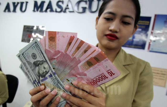 Karyawan menghitung uang di salah satu gerai penukaran uang di Jakarta, Senin (3/2/2020). Bisnis - Arief Hermawan P