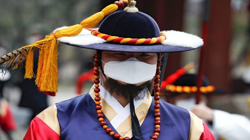 Seorang pekerja berkostum tradisional Korea mengenakan topeng pelindung untuk mencegah tertularnya virus corona selama pemeragaan ulang Royal Guards Changing Ceremony di depan Istana Deoksu di Seoul, Korea Selatan, 31 Januari 2020. - Reuters