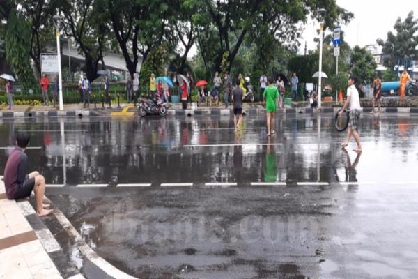 Sejumlah anak tengah bermain di pinggir jalan raya Jatibaru, Tanah Abang, Jakarta Pusat, Selasa (25/2/2020) pagi. Mereka lebih memilih bersenang-senang karena rumahnya kebanjiran. JIBI/Bisnis - Andya Dhyaksa