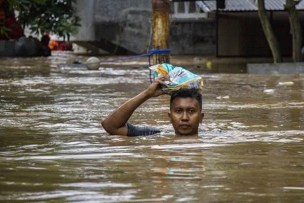 Warga berjalan melintasi banjir di Pejaten Timur, Pasar Minggu, Jakarta, Senin (5/2/2018). Banjir yang mencapai 2 meter dan merendam ratusan rumah warga tersebut akibat luapan air dari Sungai Ciliwung. - Antara/Galih Pradipta
