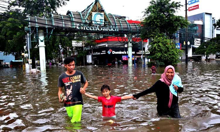 Warga melintasi banjir yang menggenangi Jalan Panjang, Kebon Jeruk, Jakarta, Selasa (25/2/2020). Hujan yang mengguyur Jakarta sejak dini hari membuat sejumlah wilayah di Ibu Kota terendam banjir. Bisnis - Eusebio Chrysnamurti