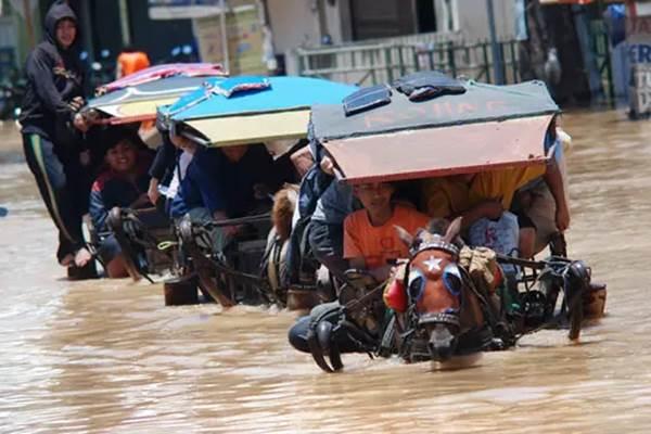 Sejumlah warga menggunakan jasa transportasi delman berusaha melintasi genangan banjir di kawasan Dayeuhkolot, Kabupaten Bandung, Jabar, Senin (3/3/2014). - ANTARA/Fahrul Jayadiputra
