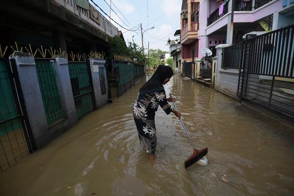 Warga membersihkan sampah saat banjir menggenangi kawasan Cipinang Melayu, Kecamatan Makasar, Jakarta Timur, Minggu (26/2). Banjir sejak Sabtu (25/2) malam tersebut akibat dari debit air Kali Sunter yang terletak di sekitar lokasi meluap dan menggenangi permukiman warga. ANTARA FOTO - Sigid Kurniawan