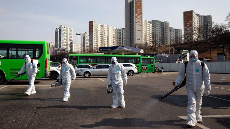 Pekerja yang mengenakan pakaian pelindung menyemprotan desinfektan di depot bus di distrik Eunpyeong Seoul pada 24 Februari 2020. - Bloomberg/Seong Jun Cho
