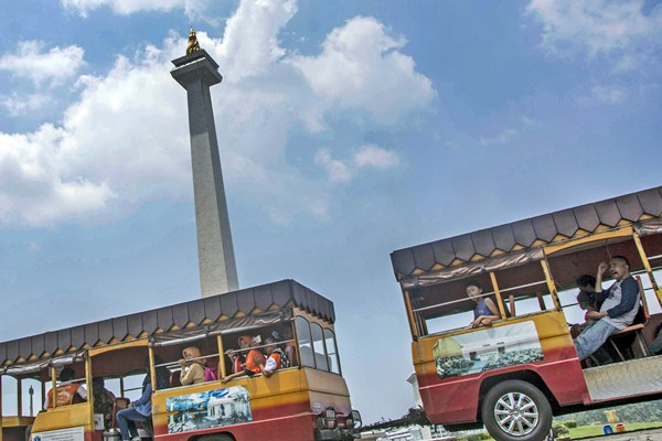 Wisatawan menikmati liburan dengan menggunakan kereta wisata di kawasan Monumen Nasional (Monas), Jakarta, Selasa (28/3). - Antara/Aprillio Akbar