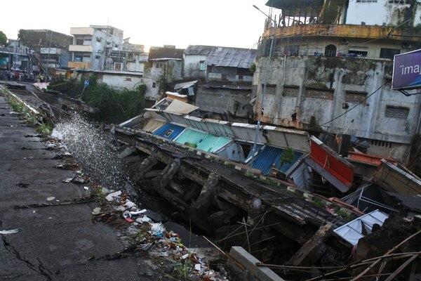 Sejumlah warga melihat pertokoan Jompo yang ambruk di Jalan Sultan Agung Jember, Jawa Timur, Senin (2/3/2020). Pertokoan Jompo ambruk akibat amblesnya Jalan Sultan Agung, salah satu jalan poros di tengah Kota Jember, dan mengancam belasan pertokoan lain di kawasan tersebut. - Antara - Seno