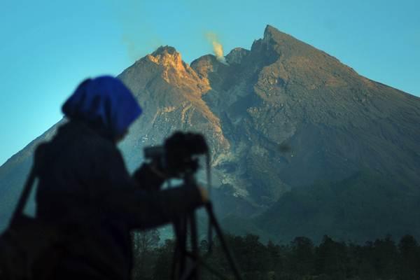 Pengunjung mengabadikan puncak Gunung Merapi yang mengeluarkan asap putih dari kawasan Balerante, Kemalang, Klaten, Jawa Tengah, Senin (7/1/2019). - ANTARA/Aloysius Jarot Nugroho