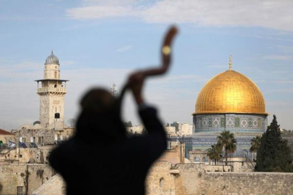 Seorang pria membentuk siluet saat meniupkan Shofar, tanduk biri-biri, dengan latar belakang Masjidil Aqsa (kanan) yang berlokasi di Kota Tua Yerusalem yang dikenal dengan Baitul Maqdis, Minggu (10/12/2017).  - Reuters