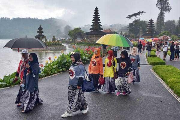 Wisatawan menikmati pemandangan di obyek wisata Pura Ulun Danu Beratan, Tabanan, Bali, Minggu (6/1/2019). - ANTARA/Nyoman Hendra Wibowo