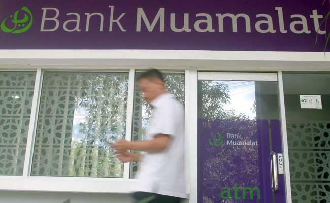 Warga melintas didekat logo bank Muamalat di Makassar, Sulawesi Selatan. Bisnis - Paulus Tandi Bone