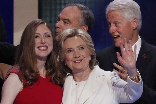 Hillary Clinton berdiri bersama putrinya Chelsea (kiri), dan suaminya Bill Clinton  - Reuters