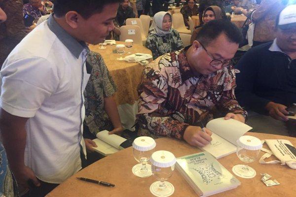 Rektor IPB Arif Satria membubuhkan tanda tangan dalam peluncuran buku Politik Sumber Daya Alam. Arif mengkritisi sentralisasi sumber daya alam (SDA) di Indonesia dan menilai desentralisasi perlu dilakukan. - Novita Sari Simamora
