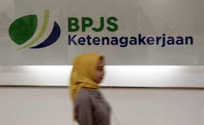 Karyawan melintas di dekat logo BPJS Ketenagakerjaan/BP Jamsostek di Jakarta. - Bisnis/Himawan L Nugraha