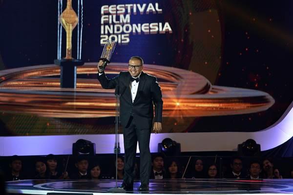 Sutradara Joko Anwar mengangkat piala citra dalam Malam Puncak Festival Film Indonesia (FFI) 2015, di Banten, Senin (23/11). - Antara
