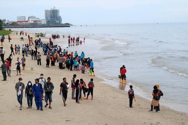 Ratusan warga berkumpul untuk membersihkan pesisir Pantai Kilang Mandiri di Balikpapan, Kalimantan Timur, Rabu (4/4/2018). Masyarakat bersama instansi pemerintah dan aparat keamanan setempat membersihkan beberapa pantai wisata di kota tersebut guna memulihkan kondisi pesisir Balikpapan yang tercemar tumpahan minyak. ANTARA FOTO - Sheravim
