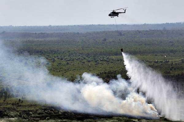 Helikopter MI-17 milik BNPB melakukan pemadaman kebakaran lahan gambut dari udara (water bombing) di Desa Lebak Deling, Pangkalan Lampam, Ogan Komering Ilir (OKI), Sumatra Selatan, Kamis (3/8). - ANTARA/Nova Wahyudi