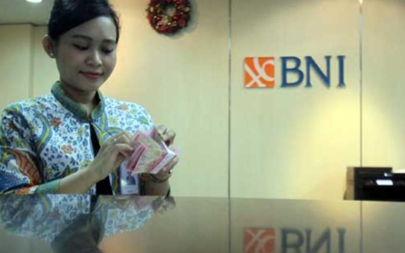 Petugas teller PT Bank Negara Indonesia (Persero) Tbk. (BNI) menghitung uang di salah satu kantor cabang BNI di Jakarta. Bisnis / Arief Hermawan P
