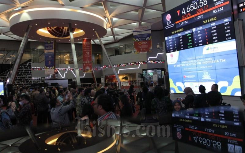 Pengunjung mengamati layar monitor yang menampilkan perdagangan harga saham di lantai PT Bursa efek Indonesia di Jakarta, Jumat (13/3/2020). Indeks Harga Saham Gabungan (IHSG) resmi disuspensi setelah 15 menit perdagangan dimulai. Indeks Harga Saham Gabungan (IHSG) parkir di 4.650,58 melemah 5,01 persen atau 245,17 poin. Bisnis - Dedi Gunawan