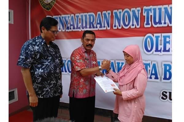 Wali Kota Surakarta FX Hadi Rudyatmo (tengah) didampingi Dirut Bank Jateng Supriyatno (kiri) secara simbolis memberikan bantuan nontunai pangan dan sosial kepada warga di Kratonan, Rabu (5/10/2016). - Bisnis/Pamudji Tri Nastiti