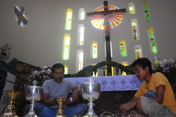 Dua orang warga Katolik membersihkan peralatan ibadah misa di Gereja Katolik Santo Petrus, Solo, Jawa Tengah, Kamis (22/12).  - Antara