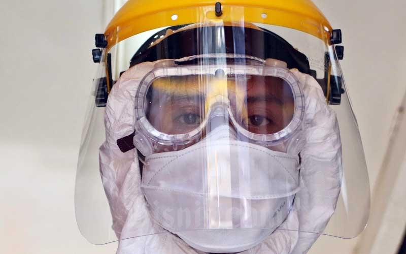 Petugas menggunkan pakaian khusus saat melakukan penyemprotan disinfektan pada gerbong kereta api di Stasiun Pasar Senen, Jakarta, Minggu (15/3/2020). - Bisnis/Eusebio Chrysnamurti\\n