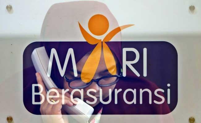 Karyawan melintasi logo-logo perusahaan asuransi di Kantor Asosiasi Asuransi Umum Indonesia (AAUI), Jakarta, Selasa (11/02/2020). Bisnis - Eusebio Chrysnamurti