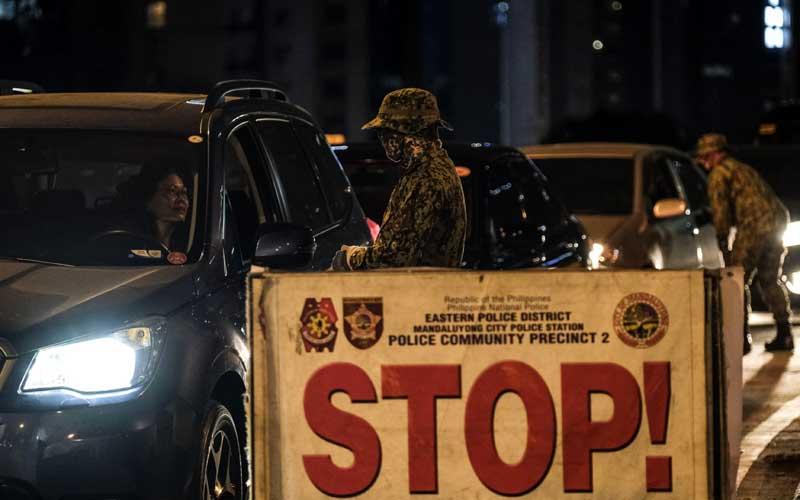Anggota Kepolisian Nasional Filipina menghentikan kendaraan di pos pemeriksaan di Makati-Mandaluyong Bridge saat diberlakukan jam malam karena corona virus di Kota Mandaluyong, Metro Manila, Filipina, Senin (16/3/2020). Bloomberg - Veejay Villafranca