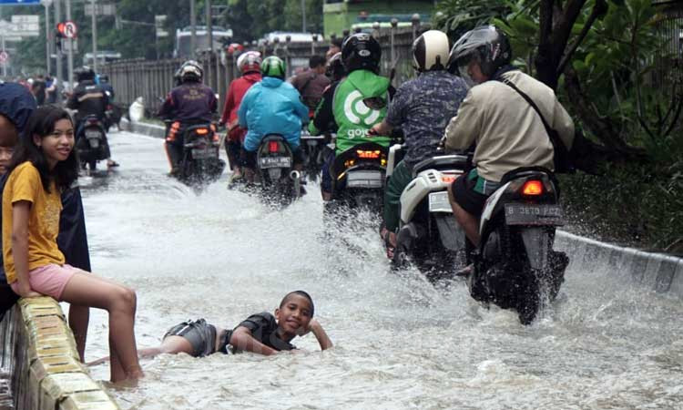 Ilustrasi. Warga beraktifitas saat banjir menggenangi Jalan Gunung Sahari, Jakarta, Selasa (25/2/2020). Bisnis - Himawan L Nugraha
