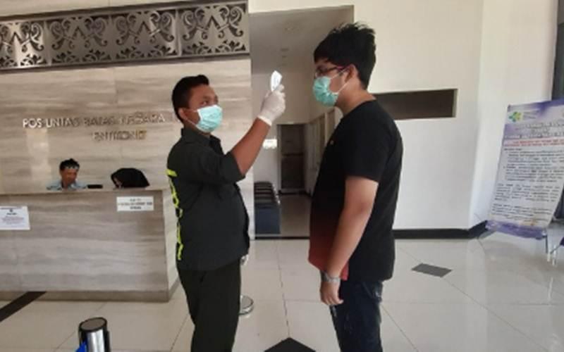 Ilustrasi-Seorang petugas Kantor Kesehatan Pelabuhan (KKP) Entikong mengukur suhu tubuh pelintas batas yang hendak ke Malaysia di Pos Lintas Batas Negara (PLBN) Entikong di Kabupaten Sanggau, Kalimantan Barat, Jumat (13/3/2020). - ANTARA/AGUS ALFIAN