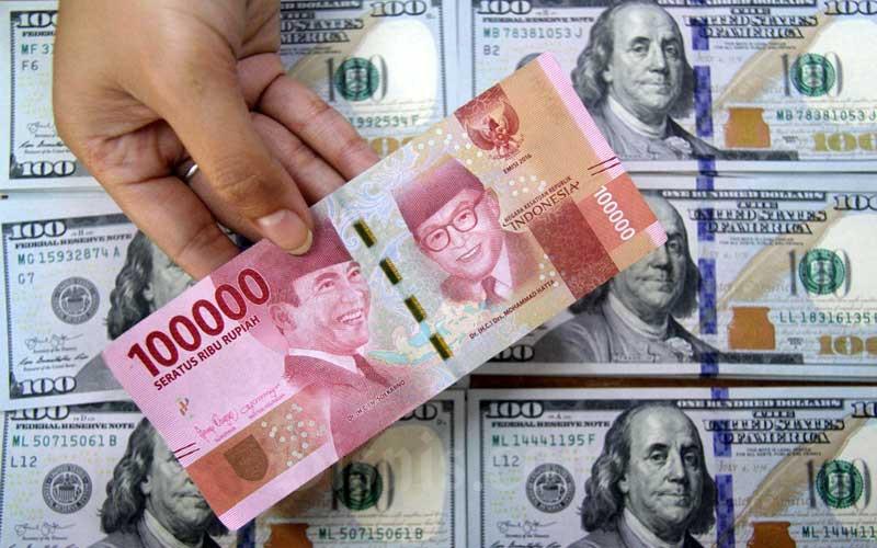Petugas menunjukkan uang rupiah dan dolar AS di salah satu gerai penukaran mata uang asing di Jakarta, Senin (16/3/2020). Bisnis - Arief Hermawan P