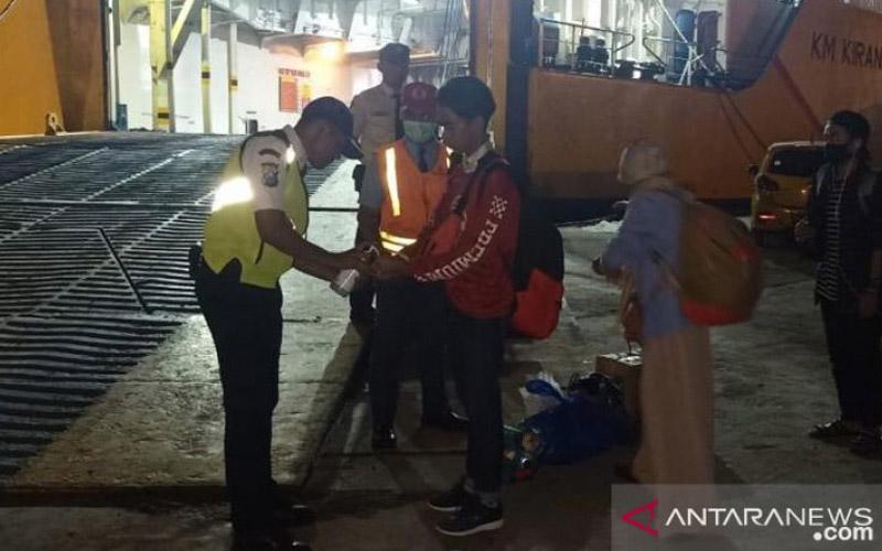 Petugas PT Dharma Lautan Utama (DLU) menyemprotkan cairan anti septik kepada penumpang saat naik ke atas kapal. - ANTARA/Firman