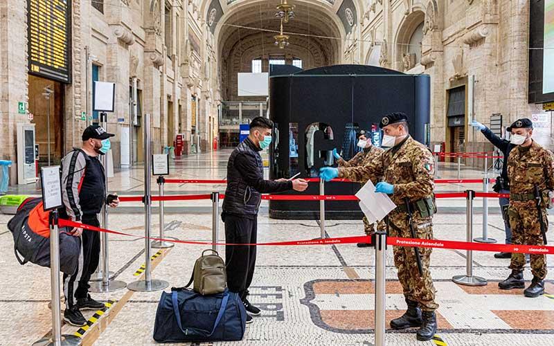 Warga menyerahkan dokumen sertifikasi dan identifikasi kepada seorang anggota militer di Stasiun Pusat di Milan, Italia, Kamis (12/3/2020). Italia menghentikan kehidupan normal dan hanya memberikan akses terhadap layanan-layanan penting untuk membendung penyebaran virus corona yang mematikan. Bloomberg - Alberto Bernasconi
