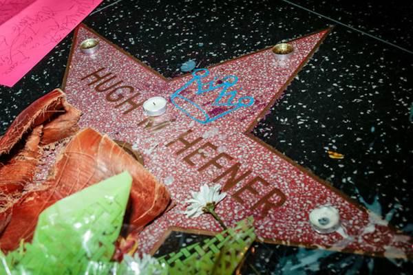 Karangan bunga dan lilin ditaruh di atas lambang bintang bertuliskan nama pendiri Playboy Hugh Hefner