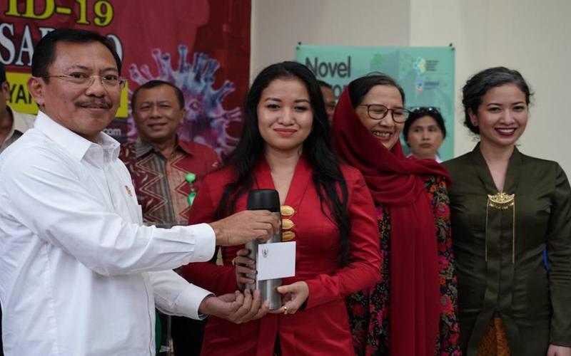 Menteri Kesehatan Terawan Agus Putranto (kiri) memberikan jamu dari Presiden Joko Widodo kepada pasien positif COVID-19 yang telah dinyatakan sembuh di RSPI Sulianti Saroso, Jakarta, Senin (16/3/2020). Pasien positif COVID-19 kasus nomor 01, 02 dan 03 telah dinyatakan sembuh. ANTARA FOTO - Humas Kementerian Kesehatan
