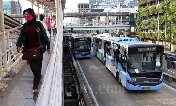 Penumpang melewati tangga untuk menaiki bus transjakarta di Halte Harmoni, Jakarta, Selasa (3/3/2020). Bisnis - Eusebio Chrysnamurti