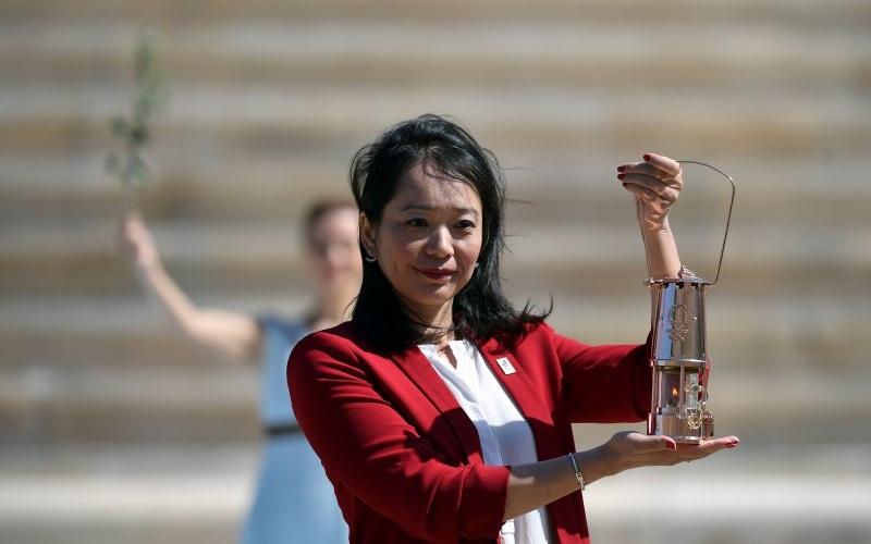 Mantan atlet renang Jepang Imoto Naoko menunjukkan api Olimpiade yang berada di dalam wadah ketika upacara serah terima di Panathenaic Stadium, Athena, Yunani, Kamis (19/3/2020) - Antara.