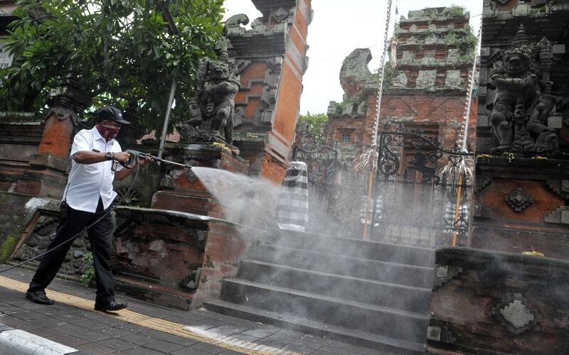 Petugas menyemprotkan cairan disinfektan di kawasan Jalan Gajah Mada, Denpasar, Bali, Rabu (18/3/2020). Penyemprotan disinfektan di sejumlah ruas jalan protokol di Denpasar tersebut dilakukan sebagai upaya untuk mencegah penyebaran Covid-19. - Antara/Fikri Yusuf