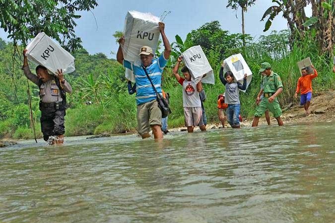 Petugas memanggul kotak suara melewati sungai menuju Tempat Pemungutan Suara (TPS) terpencil di Dusun Nampu, Desa Pojok Klitih, Kecamatan Plandaan, Jombang, Jawa Timur, Selasa (16/4/2019). - ANTARA/Syaiful Arif