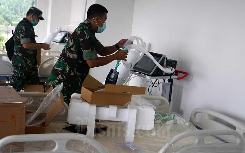 Petugas mempersiapkan sarana dan prasarana rumah sakit darurat penanganan Covid-19 di Wisma Atlet Jakarta, Minggu (22/3/2020). Bisnis - Abdurachman
