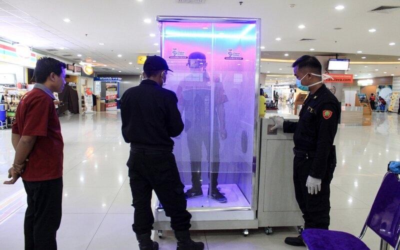 Penumpang diperiksa di ruang sterilisasi (Sterilization Chamber) yang terpasang di Terminal 2 Bandara Internasional Juanda di Sidoarjo, Jawa Timur, Minggu (22/3/2020). Pemasangan
