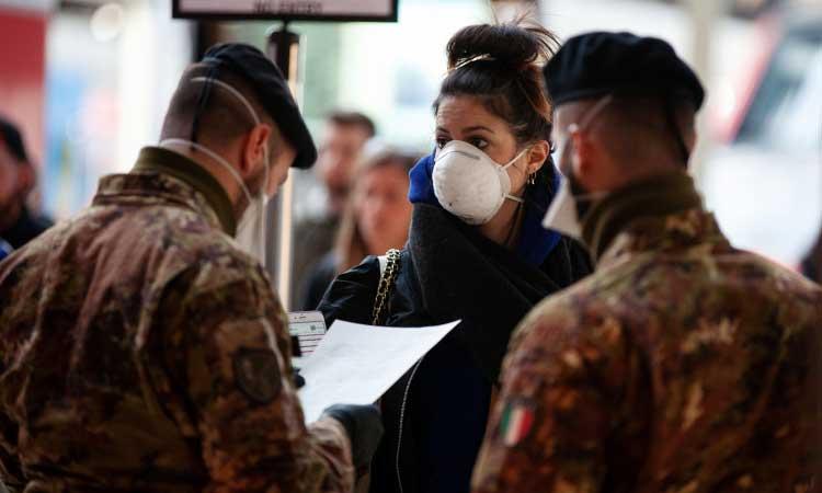 Anggota militer memeriksa formulir otorisasi perjalanandi stasiun kereta api Centrale di Milan, Italia, Selasa (10/3/2020). Italia menjadi negara pertama yang mencoba melakukan kebijakan lock down (penguncian) untuk menghentikan penyebaran virus corona. Bloomberg - Camilla Cerea
